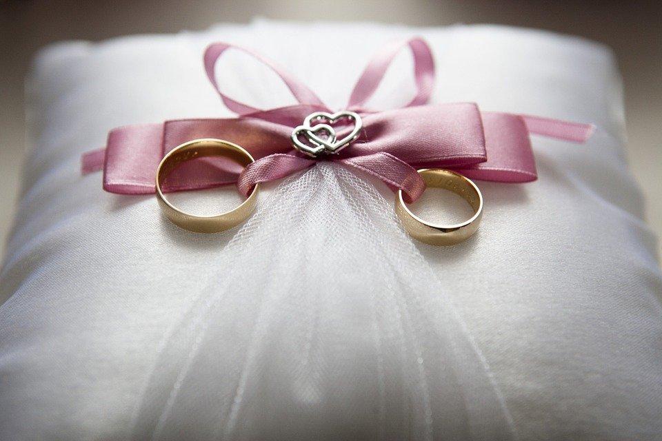 anelli per il giorno delle nozze, fedi nuziali su un cuscino bianco e legate da un nastrino di raso rosa